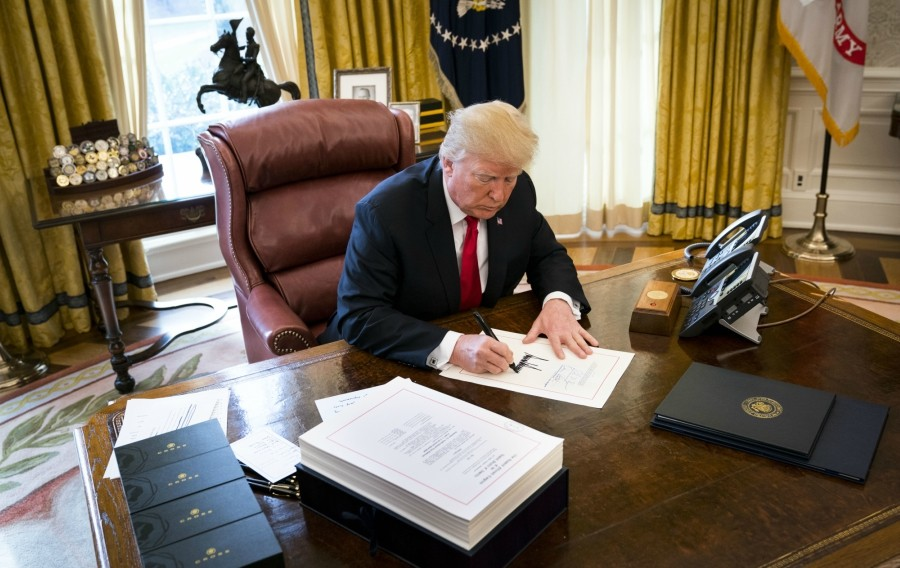 President Donald Trump signs a sweeping tax bill in the Oval Office of the White House, in Washington, Dec. 22, 2017. Trump signed the bill that Republicans promise will benefit the middle class, despite warnings from Democrats that the new law could be harmful to the country. - DOUG MILLS/THE NEW YORK TIMES
