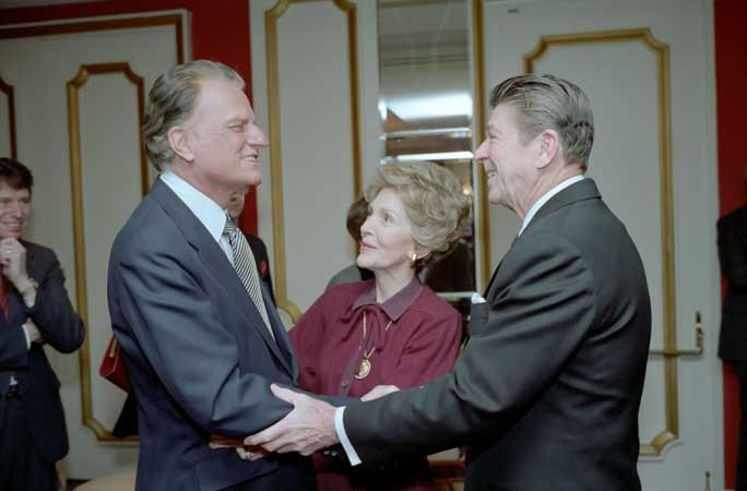 President Ronald Reagan and first lady Nancy Reagan greet Graham at the National Prayer Breakfast of 1981. - WHITE HOUSE PHOTO