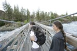Brendan Love, left, his girlfriend Ryann Ensrud and their 1-year-old cat Fisher stand on the Bowl and Pitcher suspension bridge at Riverside State Park in Spokane, Wash., Friday, June 15, 2018. (Young Kwak/The Inlander)
