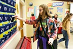 13-year-old Emelia Sanburn picks up her cell phone from a holder after class.