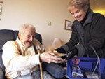 Judy Reilly, right, hands a Meals on Wheels delivery to 87-year-old Emanual Kennedy.