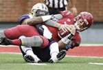 Washington linebacker Keishawn Bierria, left, brings down Washington State quarterback Luke Falk during the first half.
