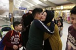 12-year-old Omar Kahiri a refugee from Iraq who arrived on a flight Saturday hugs his cousin Asma Abdul Almhos.