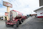 A gas truck adds fuel to a downtown Spokane gas station near the Tiki Lodge.