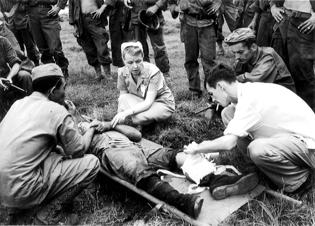 U.S. Army Nurse Frankie Lewey treating a wounded man shortly after the February 3, 1945, liberation of Santo Tomas Internment Camp in Manila, Philippines.