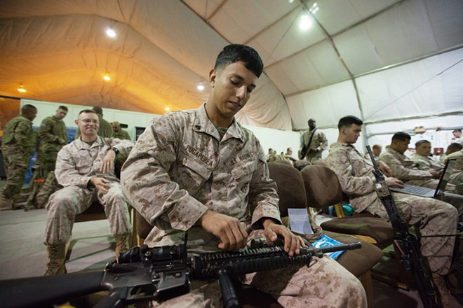 US Marine Corps First Combat Engineering Battalion Corporal Rene Pugapera cleans his rifle while waiting for a bus to pick him up to an airplane to send him home, at the Passenger Terminal. - YOUNG KWAK