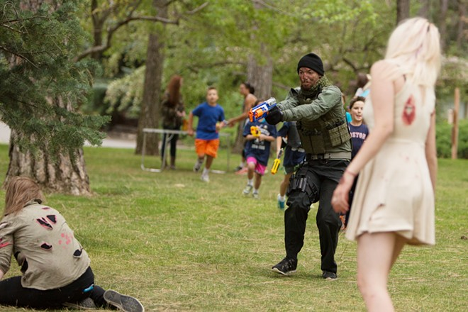 Volunteer Bryce Gray, second from the right, shoots a zombie while leading a group of participants. - YOUNG KWAK