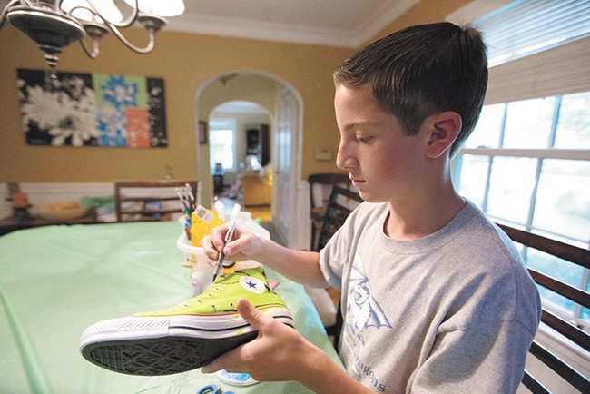 Volunteer Dylan Soth puts his creativity to work on a pair of Converse. - YOUNG KWAK
