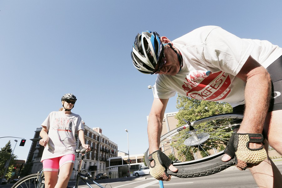 Volunteer Greg Welton, from North Division Bicycle Shop, right, fixes a flat for Miranda Moen. - YOUNG KWAK