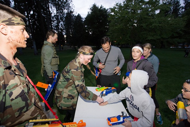 Volunteer Halie Olney, center, hands 9-year-old Owen Ames nerf gun ammunition. - YOUNG KWAK