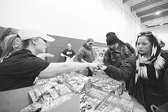 Volunteer Jody Jones, left, hands food items to Genesis Marcial, who has been homeless for 8 months, at the food bank during Homeless Connect, held at the Salvation Army. - YOUNG KWAK