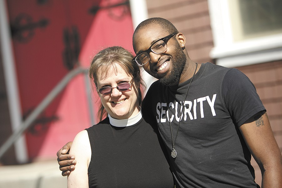 Volunteer Tasheem Gresham, left, and Rev. Kris Christensen in front of the Holy Trinity Chapel. Built in 1895, it's the oldest church in the city. - YOUNG KWAK