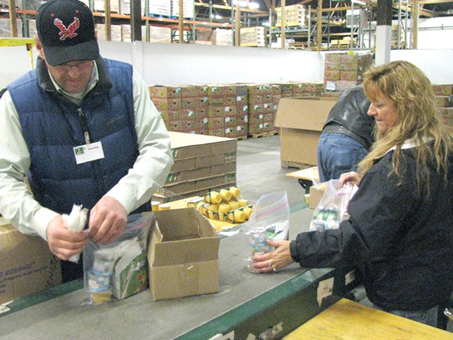 Volunteers pack the 468 weekend food packs that the Second Harvest Food Bank distributes every week.