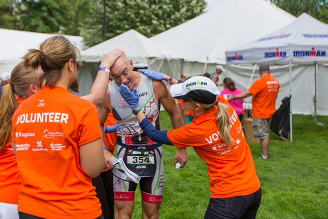 Volunteers rub sunscreen on John Poisson, who finished 96th overall. - MATT WEIGAND