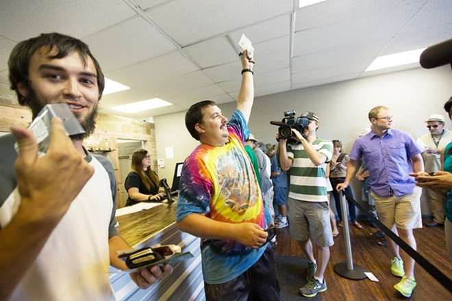 First customer Mike Boyer, center, displays his purchase at Tuesday's opening of Spokane Green Leaf. - YOUNG KWAK PHOTO