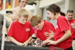 Wilson Elementary School 4th grader Thomas Schermerhor, center, prepares his robot for an obstacle course as teammates Brendan O'Rourk, left, and Mishelle Koston look on, during the 1st Lego League competition.