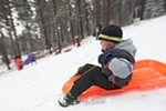 With just enough snow for sledding, 7-year-old Noah Wright and other local children took to the slopes Saturday at Underhill Park in East Spokane.