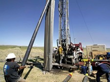 Workers at a natural gas well In Wyoming. - ROBERT NICKELSBERG PHOTO/GETTY IMAGES