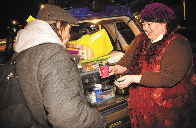 """You're a saint!"" says Jimbo, a homeless Spokane man, as Joan Medina serves a warm cup of coffee to him. - JENNIFER DEBARROS"