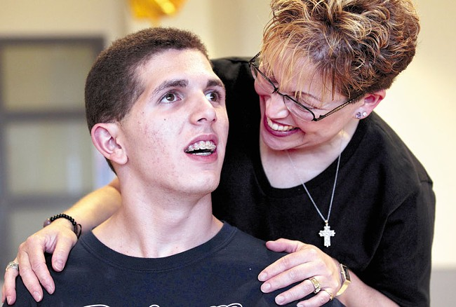Zach Lystedt with his mom, Mercedes, last June, just before he graduated from high school — and nearly five years after his head injury. - ELAINE THOMPSON PHOTO/AP