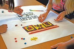 Kids work in teams to make scanable QR codes out of M&M's at Code Camp. - NATALIE WILLIAMS