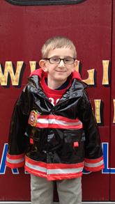 Noah in front of his favorite thing: an ambulance.