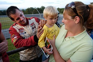 Tanya Cheney of Moretown holds her son Owen as late-model driver Dave Pembroke signs his shirt