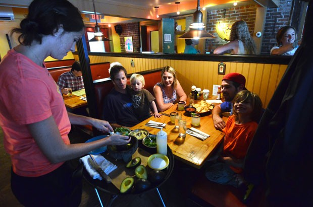 The Jones Godfrey clan, including Carter, 3, left, and Mason, 6, get tableside guacamole at Frida's in Stowe.
