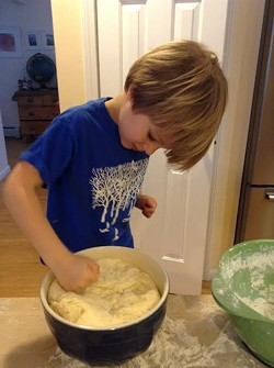 Theo happily punching the dough.