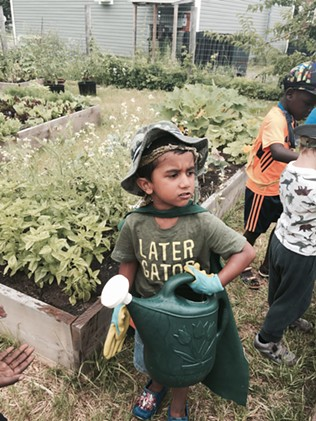 A BCS preschooler sports a superhero cape in the Archibald Neighborhood Garden - ALISON NOVAK