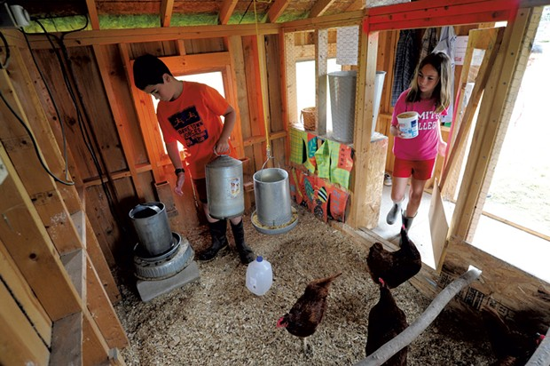 Twins Jordan and Taylor Parker-Martin, 10, feed the chickens - JEB WALLACE BRODEUR
