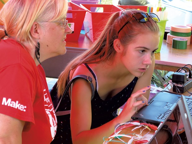 Lucie deLaBruere works with a teen on coding and circuitry at her Champlain Mini Maker Faire exhibit - MATTHEW THORSEN