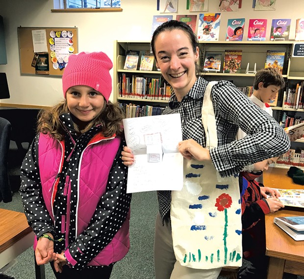 Mira gives a painted tote bag and note to our children's librarian