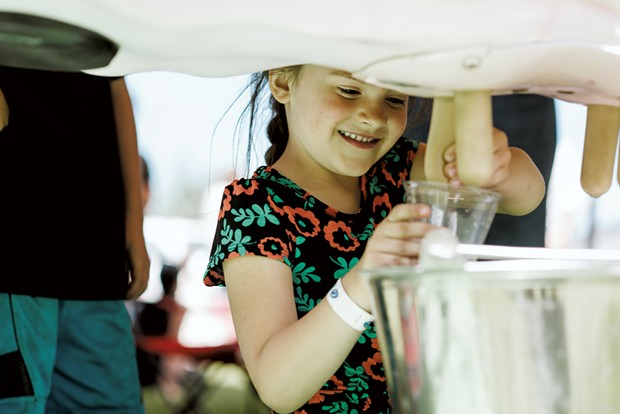 Brielle Goodwin, 5, of Sheldon, get her turn at the milking machine. - SAM SIMON