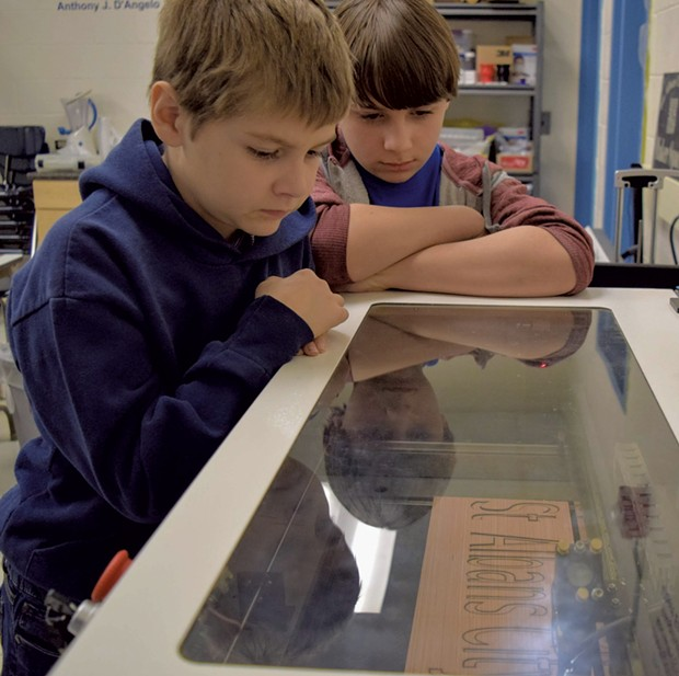 St. Albans City School students watching the laser cutter work its magic