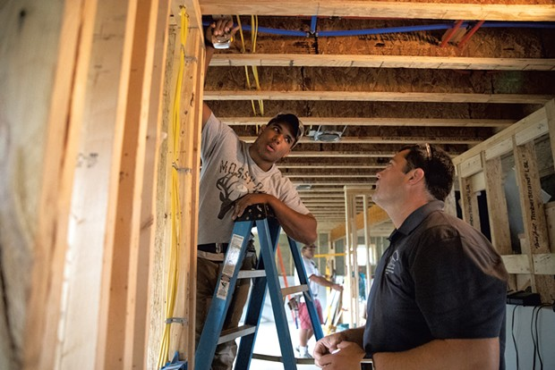 Essex High School senior Keshon Peters (left) and instructor Chris Welch discuss the measurements needed to cut ceiling drywall to fit around a corner - JAMES BUCK
