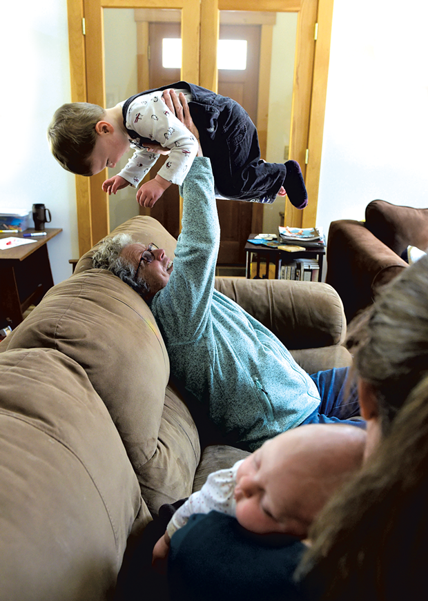 Postpartum Angel Didi Brush plays with 2-year-old Eric while his mom, Helen Sullivan, holds 7-week-old daughter Vera - JEB WALLACE-BRODEUR