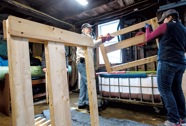Volunteers prepare to dunk a headboard in a vat of homemade wood stain - GLENN RUSSELL