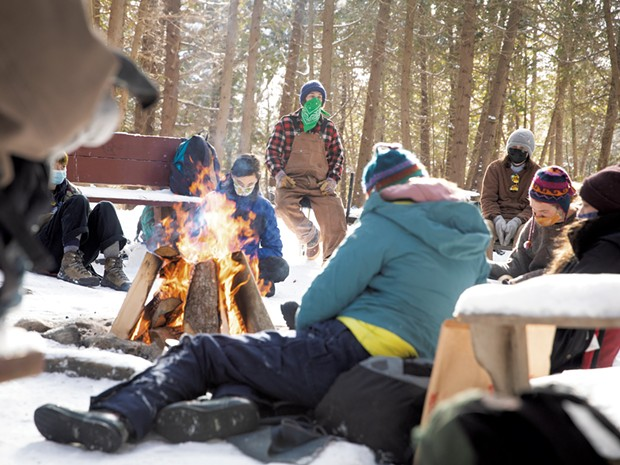 Students keeping warm at the Walden Cedar Grove, the program's base camp - CAT CUTILLO