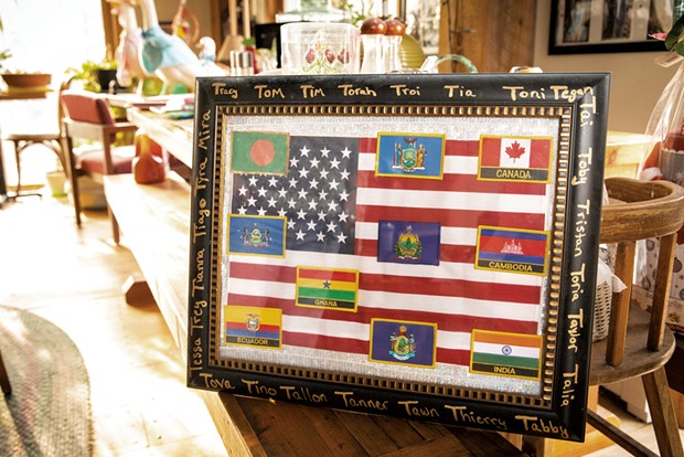 A plaque with flags showing the birth countries of Tomasi's children - CAT CUTILLO