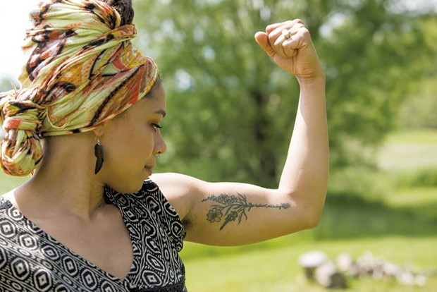 """Kia'Rae flexes her tattoo, which reads """"Life is short, art is long - CAT CUTILLO"""