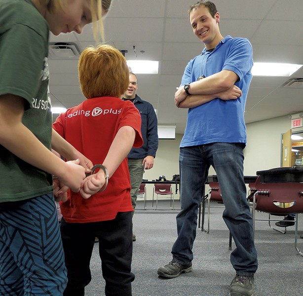 Lincoln Safran gets handcuffed by a fellow student as Officer Phillip Tremblay looks on.