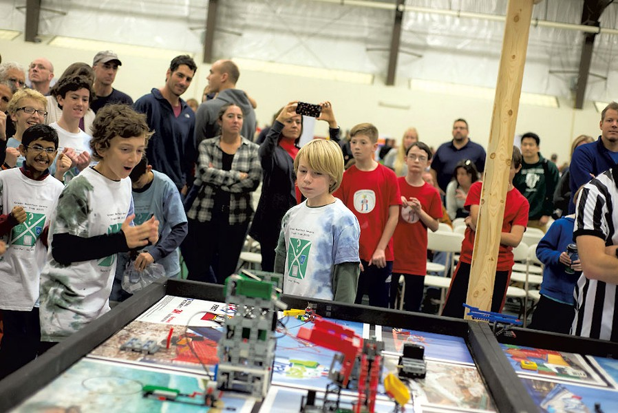 Members of the GreenMountain Gears watching asthe irrobot navigates the gameboardat the FIRST LEGO League StateChampionships last November - COURTESY OF MARK COLLIER
