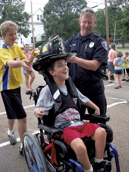 Ben tries on a firefighter's hat - COURTESY OF DEBBIE LAMDEN