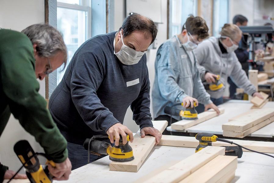 Volunteers sand wood boards before building begins - GLENN RUSSELL