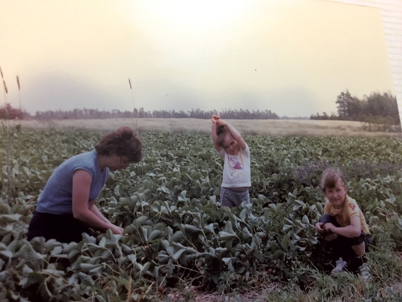 Amy (center) with her mom and sister in 1984, harvesting strawberries in Nova Scotia