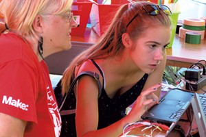Lucie deLaBruere works with a teen on coding and circuitry at her Champlain Mini Maker Faire exhibit
