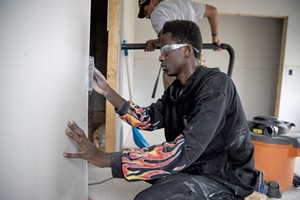 Essex High School senior Mustaf Mohamed uses a surform rasp to make drywall flush with a door frame