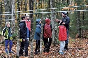 Dave Bennett (right) explains features of the sugar bush to kids from the Community Connections afterschool program, as Elise Bennett and program coordinator Drew McNaughton (second from left) look on.