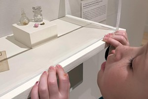 Ruby examines miniature glassware from the museum's global collection